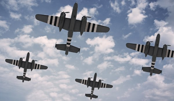 A formation of five North American B-25 Mitchells, painted with D-Day invasion stripes.