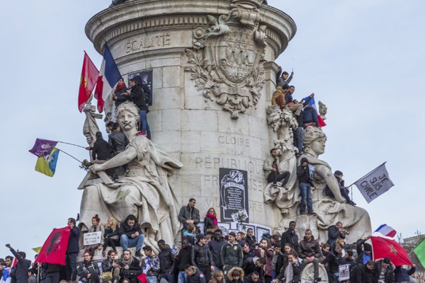"""Paris, France - January 11th, 2015: People holding signs and flags during the """"Je Suis Charlie"""" parade at Place de la Republique"""