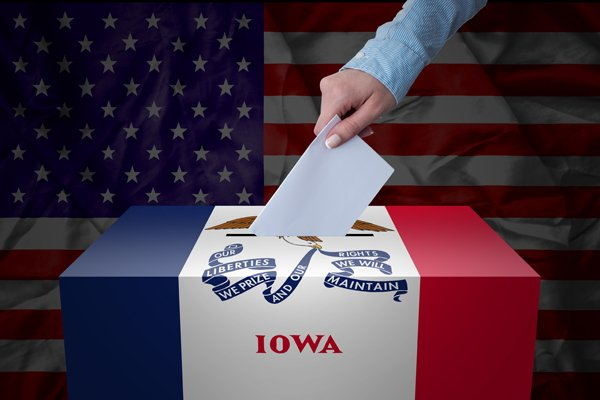 A hand casting a vote in a ballot box for an election in the Iowa, USA