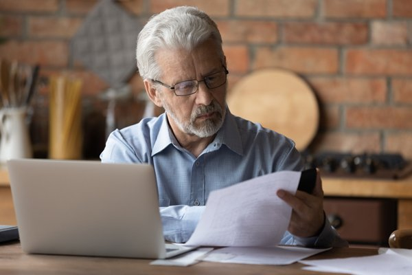 concerned man on computer reading papers